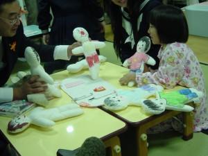 今描いたドールで一緒に遊ぶ子どもさんと佐々木(昌)会員